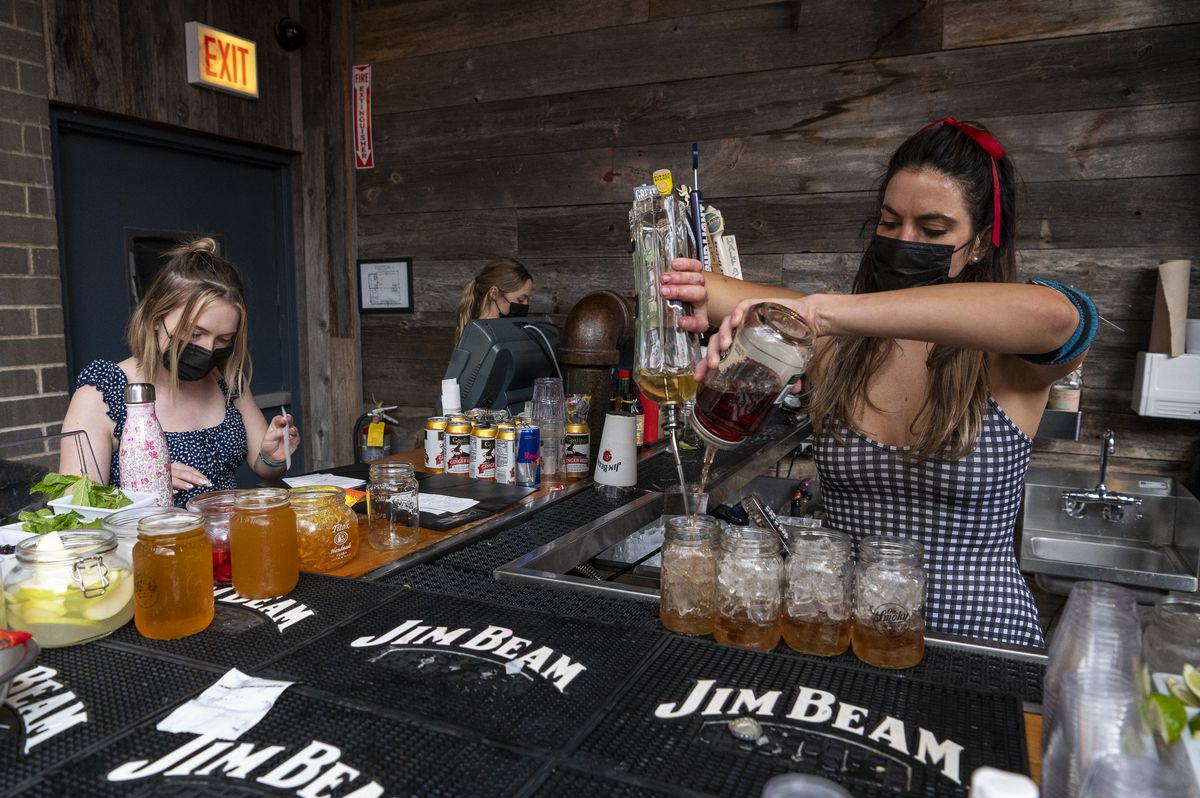 Two waitresses (left) go over orders as a bartender mixes drinks at the Old Crow Smokehouse in Wrigleyville on Friday, Sept. 3, 2021.