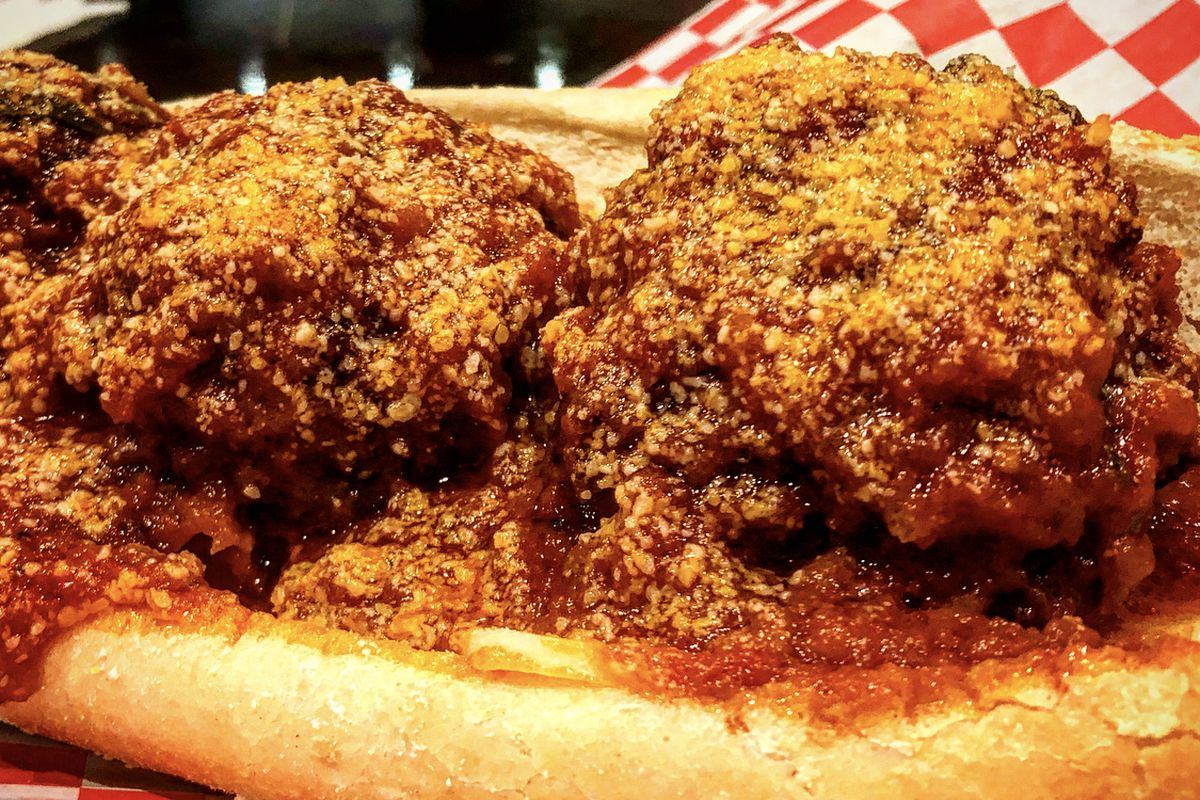 Giant brown meatballs on a bun with red sauce