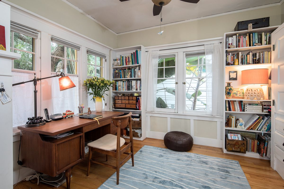 A room with a writing desk and bookshelves