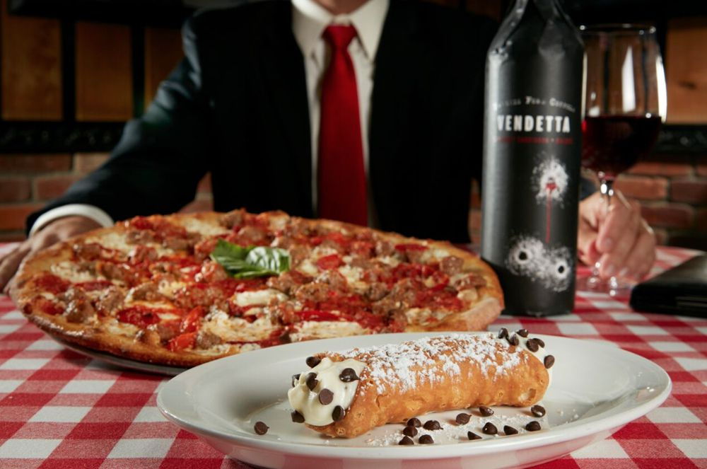 Pizza and cannoli on checkered tablecloth