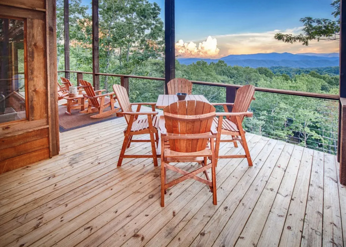 Deck with table and four chairs overlooking the mountains.