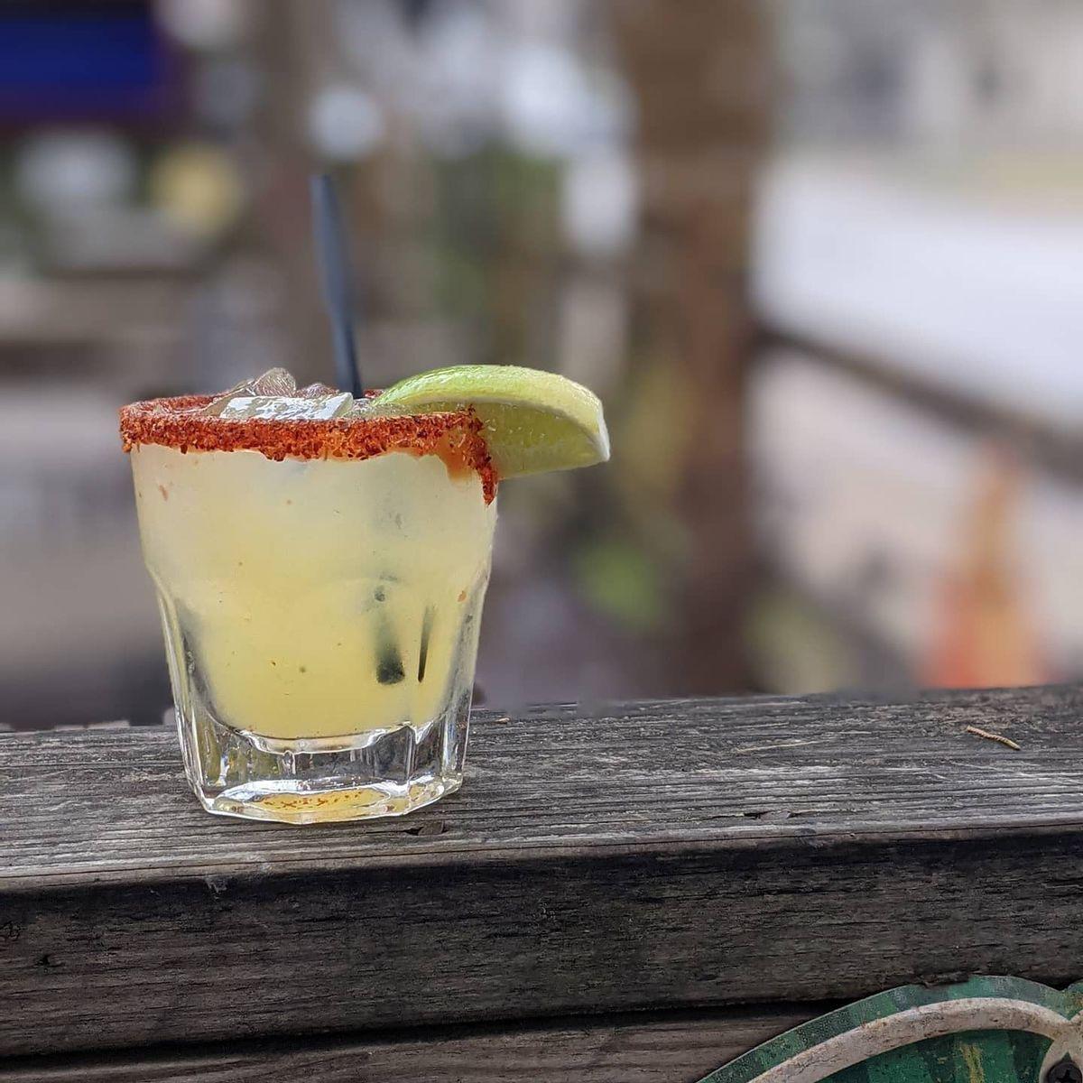 a margarita lined with tajin on a patio balcony