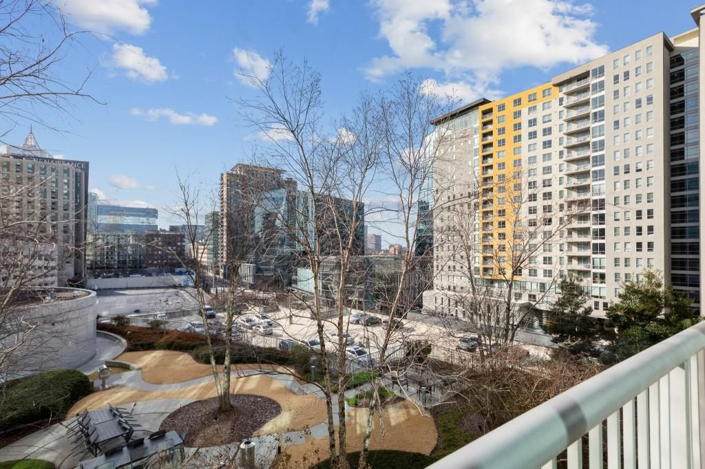 A balcony with views over Midtown Atlanta and trees.