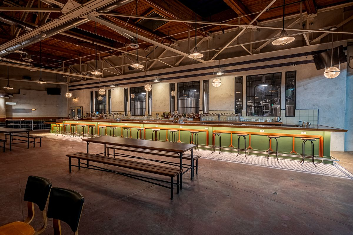 A long light green bar area inside of a dark warehouse bar.