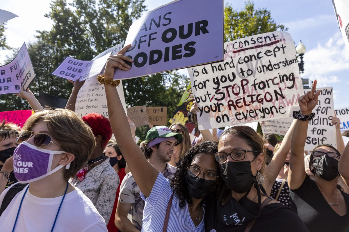 """Protesters hold signs that read, """"Stop forcing your religion on everyone,"""" and, """"Hands off our bodies."""""""
