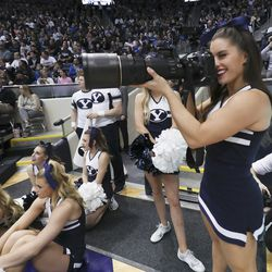 BYU cheerleader Anna Liljenquist borrows a photographer's camera in Provo on Saturday, Feb. 8, 2020. BYU won 90-76.