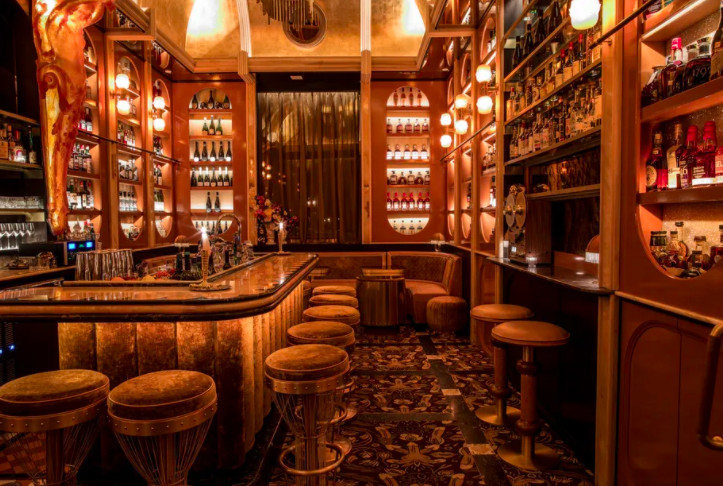 A dimly-lit bar filled with plush bar stools and booth seating.