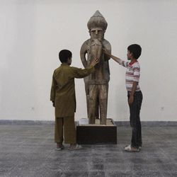 In this Tuesday, Aug. 28, 2012 photo, boys touch a statue made of wood at the National Museum of Afghanistan in Kabul. Right  down to the power cuts that frequently plunge its artifacts into shadow, the National Museum of Afghanistan is a symbol of the country's recent hardships. Its building was shelled, looted and caught fire during the 1992s civil war. Taliban extremists later smashed many centuries- old statues.