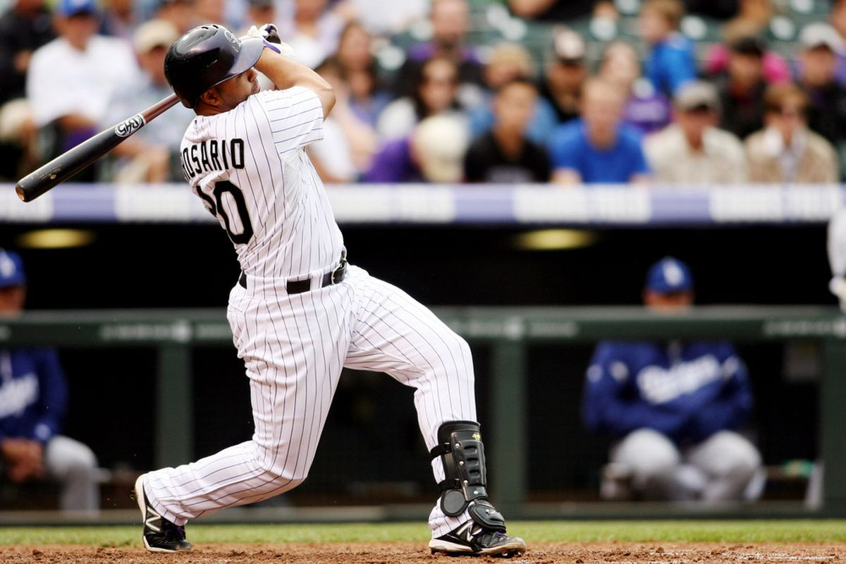 June 2, 2012; Denver, CO, USA; Colorado Rockies catcher Wilin Rosario (20) hits an RBI double during the seventh inning against the Los Angeles Dodgers at Coors Field.  The Dodgers won 6-2.  Mandatory Credit: Chris Humphreys-US PRESSWIRE