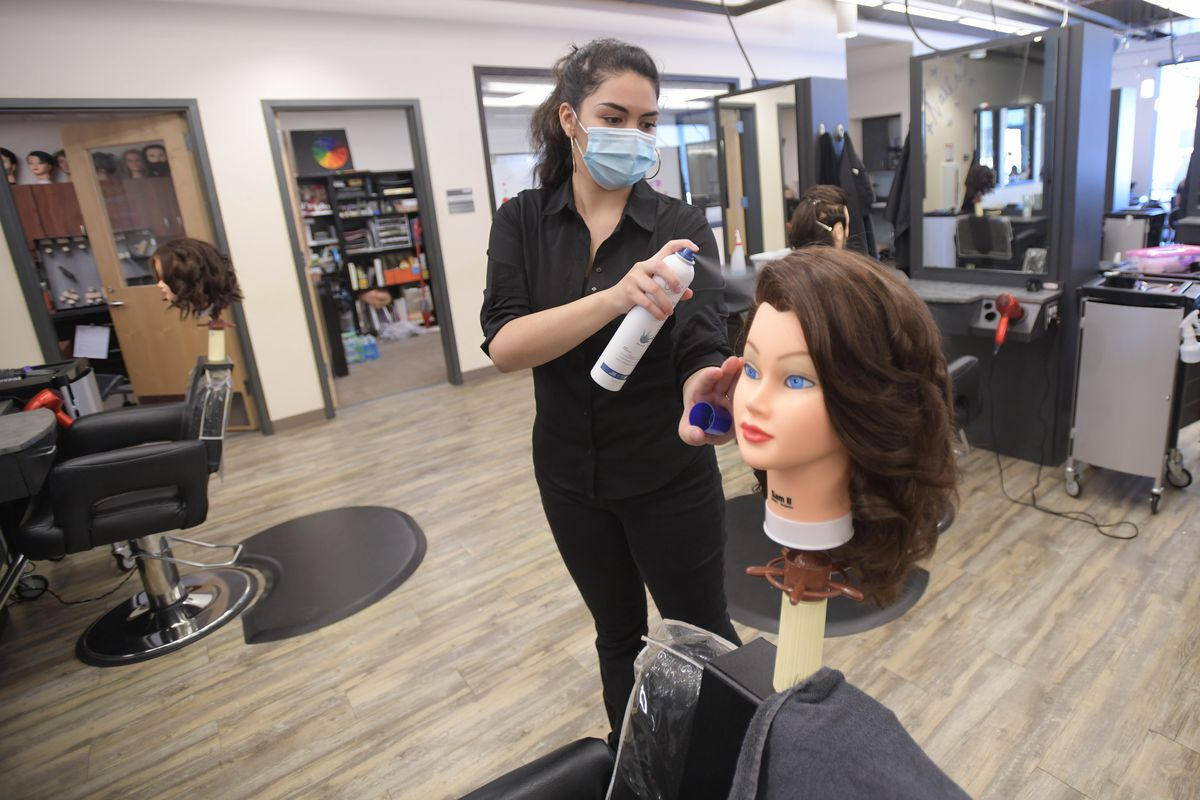 Cosmetology student practices styling on a mannequin in what appears to be an empty salon-like classroom.