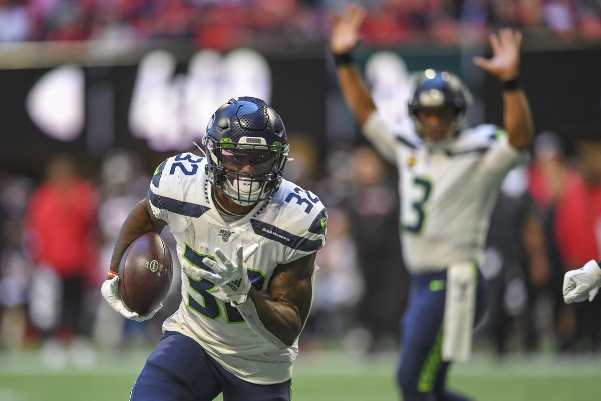 Seattle Seahawks running back Chris Carson scores a touchdown against the Atlanta Falcons as quarterback Russell Wilson reacts in the background during the first half at Mercedes-Benz Stadium.