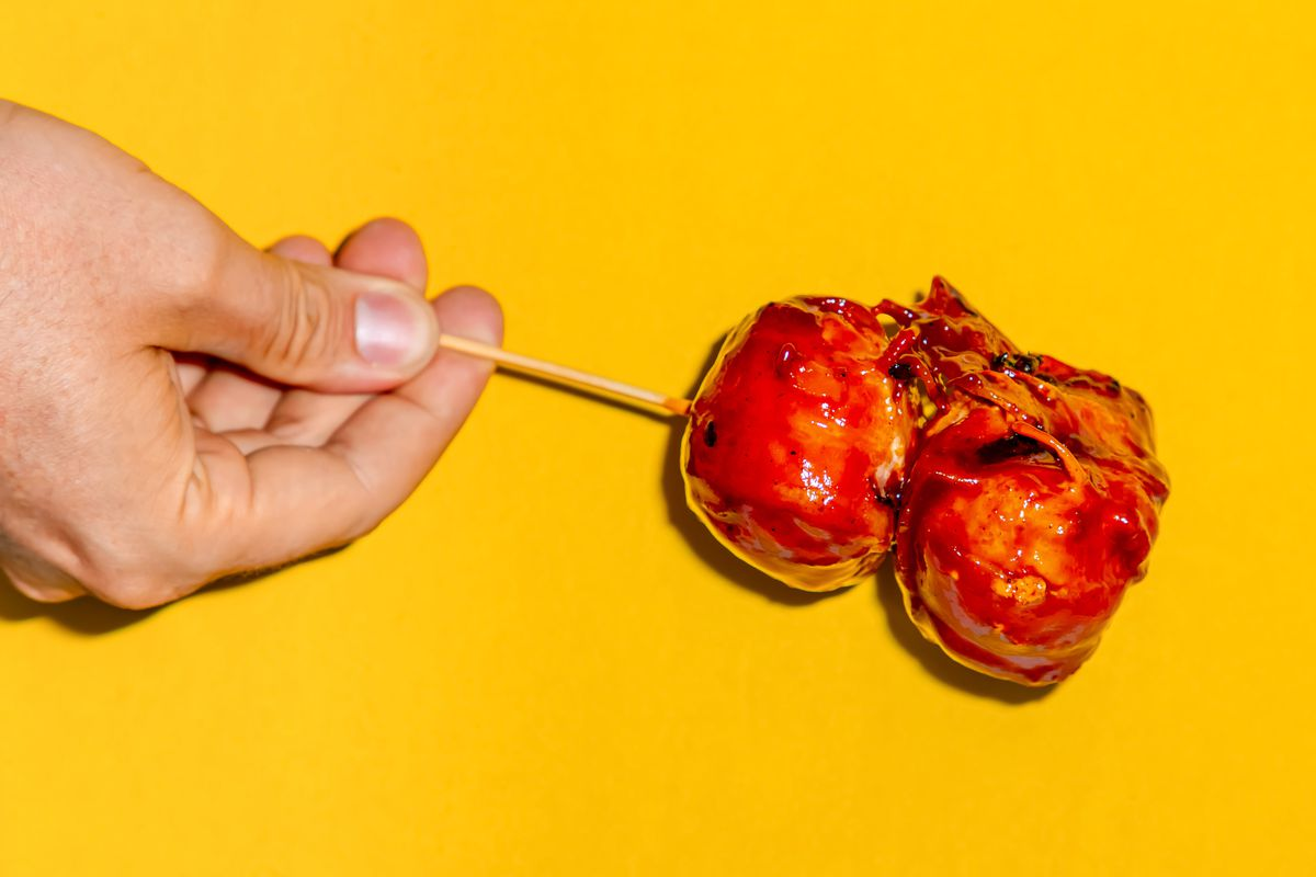 A hand holding bacon balls on a stick against a yellow background