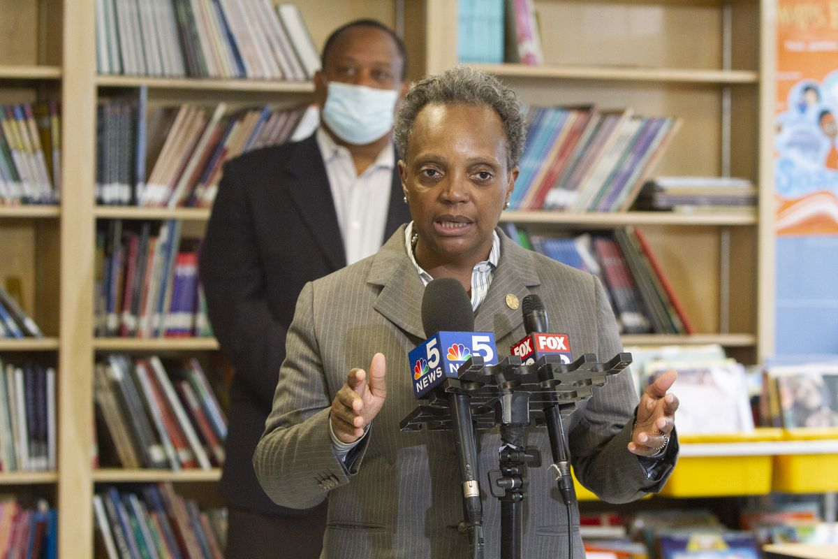 Mayor Lori Lightfoot talking into microphones at a press conference.