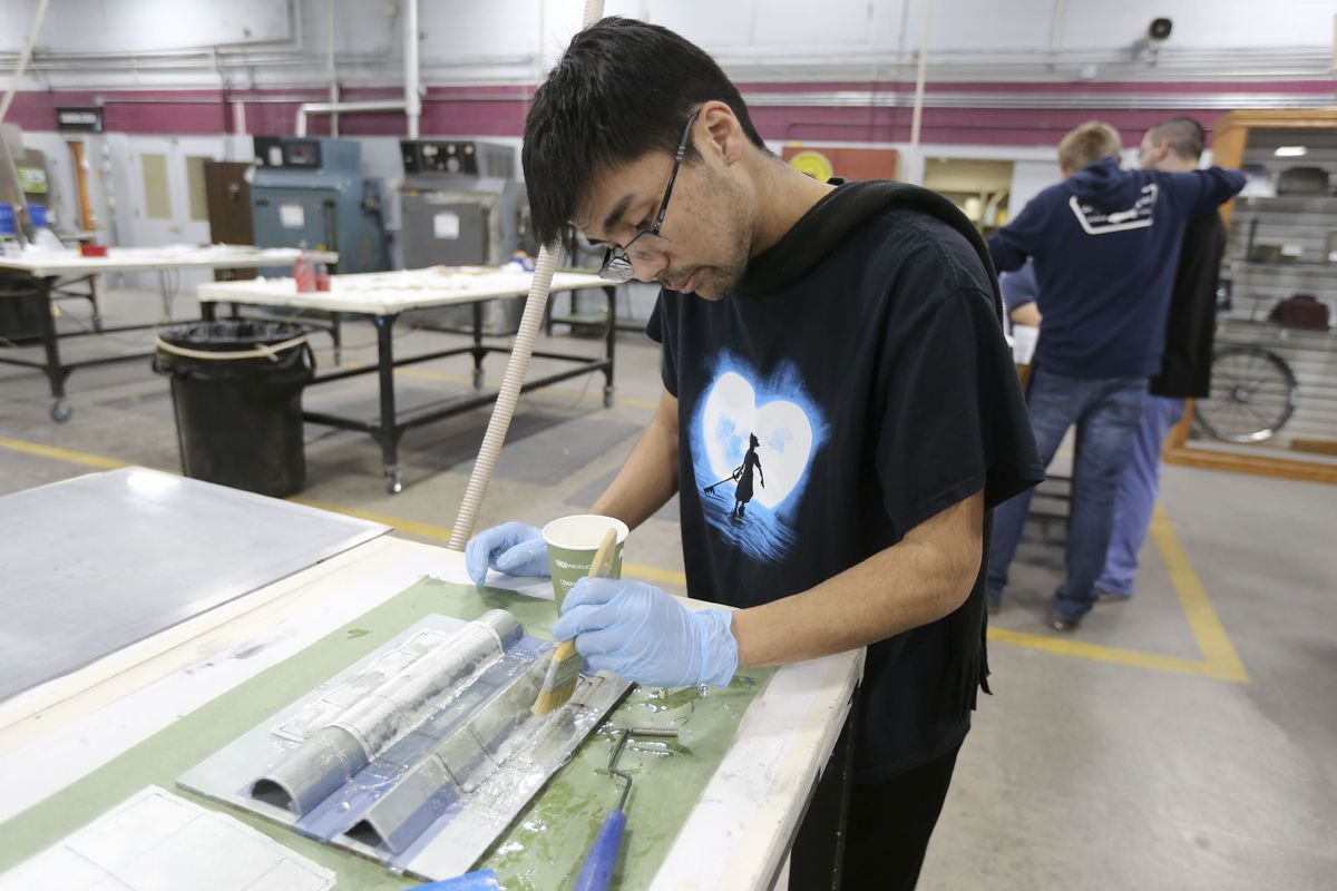 Orion Gonsalves applies epoxy to fiberglass material during a composites class at Davis Technical College in Kaysville on Wednesday, Jan. 29, 2020.