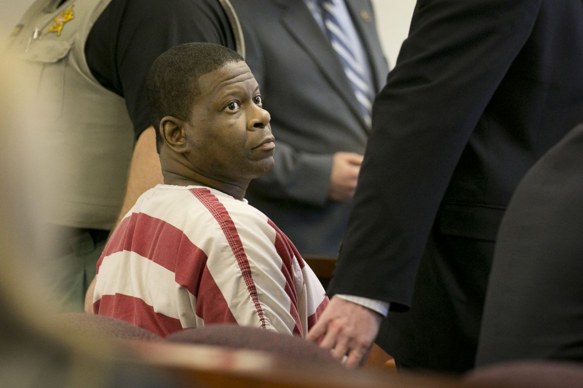 Rodney Reed sitting in a hearing surrounded by men in suits.