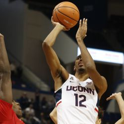 UConn's Tyler Polley (12) puts up a shot in front of a Boston University defender.