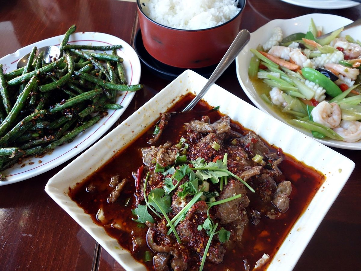 A variety of plates, including a beef dish and a side of green beans, from Seven Stars Pepper.