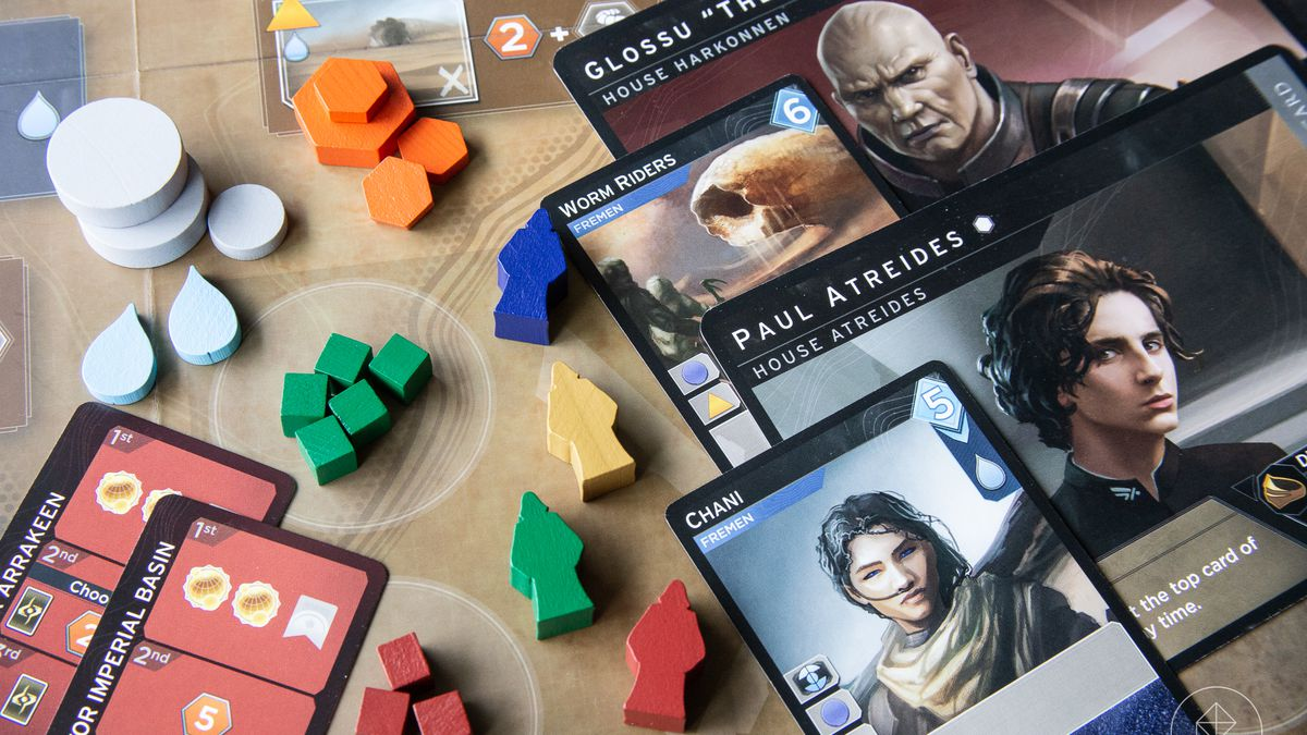 Game pieces from Dune: Imperium laid out on the game board, which is a map of the planet Arrakis.