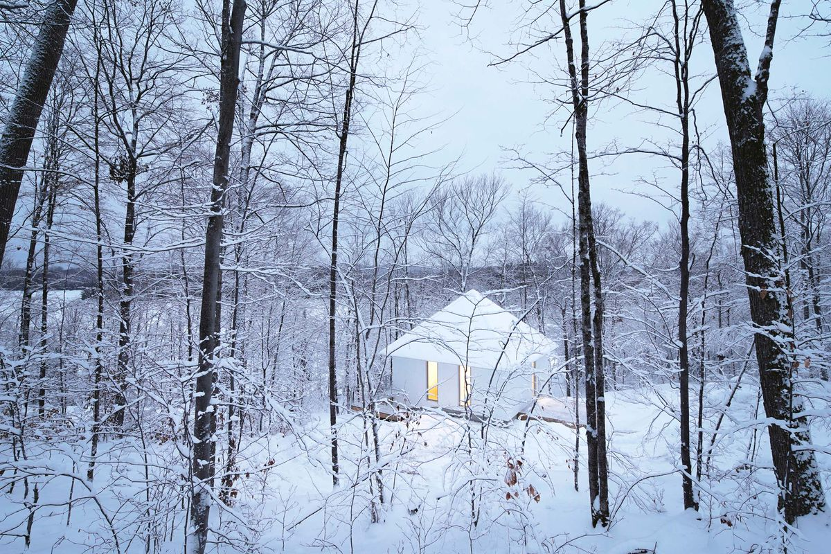Small cabin in the woods, covered in snow.