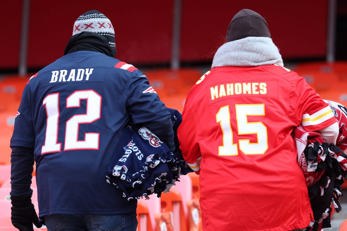 A man wearing a Tom Brady jersey, left, and a woman wearing a Patrick Mahomes jersey are pictured in the stands before the start of the 2019 AFC Championship Game.