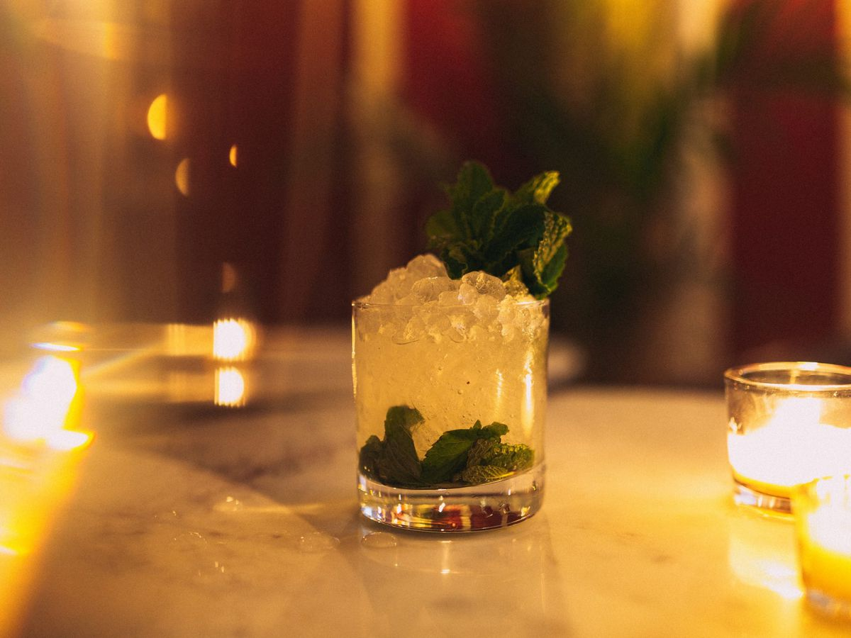 A chartreuse cocktail with fresh herbs smashed at the bottom, surrounded by lit candles
