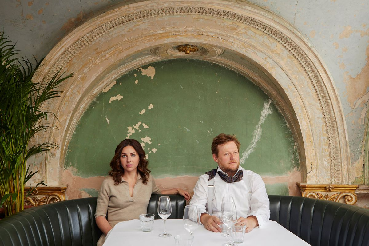 Florence Knight (left) and Jonny Gent (right) sit in a banquette with a white tablecloth and wine glasses, backed by a distressed green fresco with an arch