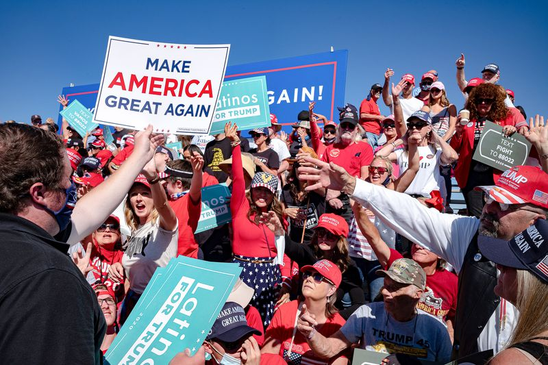 """Trump supporters at a rally hold signs that read """"Make America great again"""" and """"Latinos for Trump."""""""