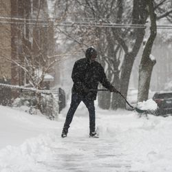 A man shovels the sidewalk near North Ridge Boulevard and West Birchwood Avenue in Rogers Park after more than three inches of snow fell during a winter storm that moved through the Chicago area overnight, Tuesday morning, Jan. 26, 2021.