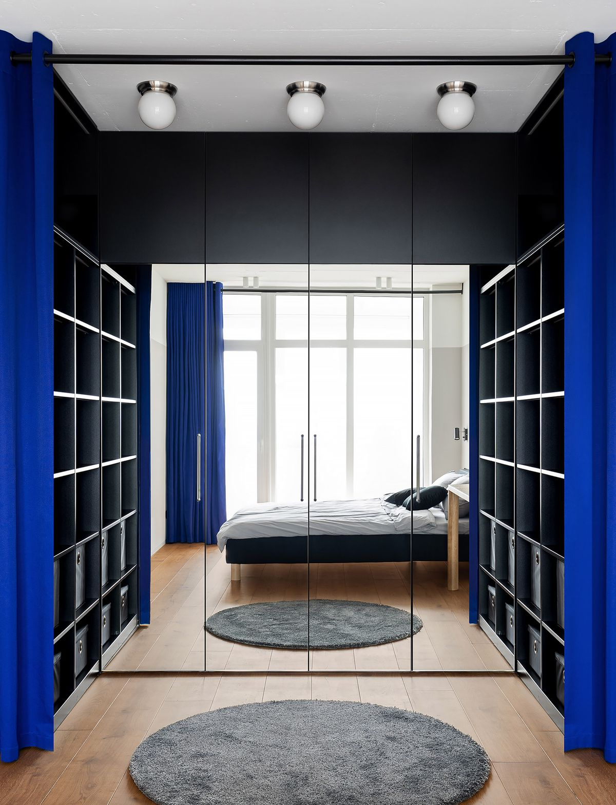 Wardrobe surrounded by blue curtains.