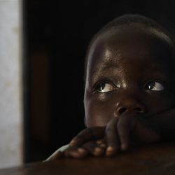 """In this photo taken Friday, April 27, 2012, daughter Betty, 3, looks up at her mother Adye Sunday, 25, unseen, who was abducted when she was 13 by Lord's Resistance Army (LRA) leader Joseph Kony and forced to be one of his dozens of """"wives"""" and says he's also the father of her two children, at a center set up to help those who have left or fled the LRA, in Gulu, Uganda. Adye Sunday isn't sure about the calls to kill or capture LRA leader Joseph Kony, who inspires conflicted thoughts among some people in northern Uganda, despite more than 3,000 children being abducted by the LRA since 2008, according to the U.N. and Human Rights Watch. (AP Photo/Ben Curtis)"""