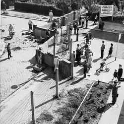 West Berliners at right watch East German construction workers erect a wall across Wildenbruchstrasse and Heidelbergerstrasse in West Berlin in August 1961. Built with barbed wire and concrete, the Berlin Wall, stretching for about 30 miles, was a Cold War symbol which separated East and West Berlin, preventing people from leaving East Germany. It stood for 28 years as a division between the Soviets and the Allies. The wall was torn down after Communism collapsed in 1989.