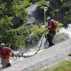 Members of the Salt Lake County Search and Rescue team help try to recover the body of a 22-year-old hiker who fell in Bell Canyon on Monday, June 5, 2017. Siaosi Brown's body was spotted in the lower falls of the canyon. His body was trapped on some logs in the middle of the waterfall, Unified Police Lt. Brian Lohrke said.