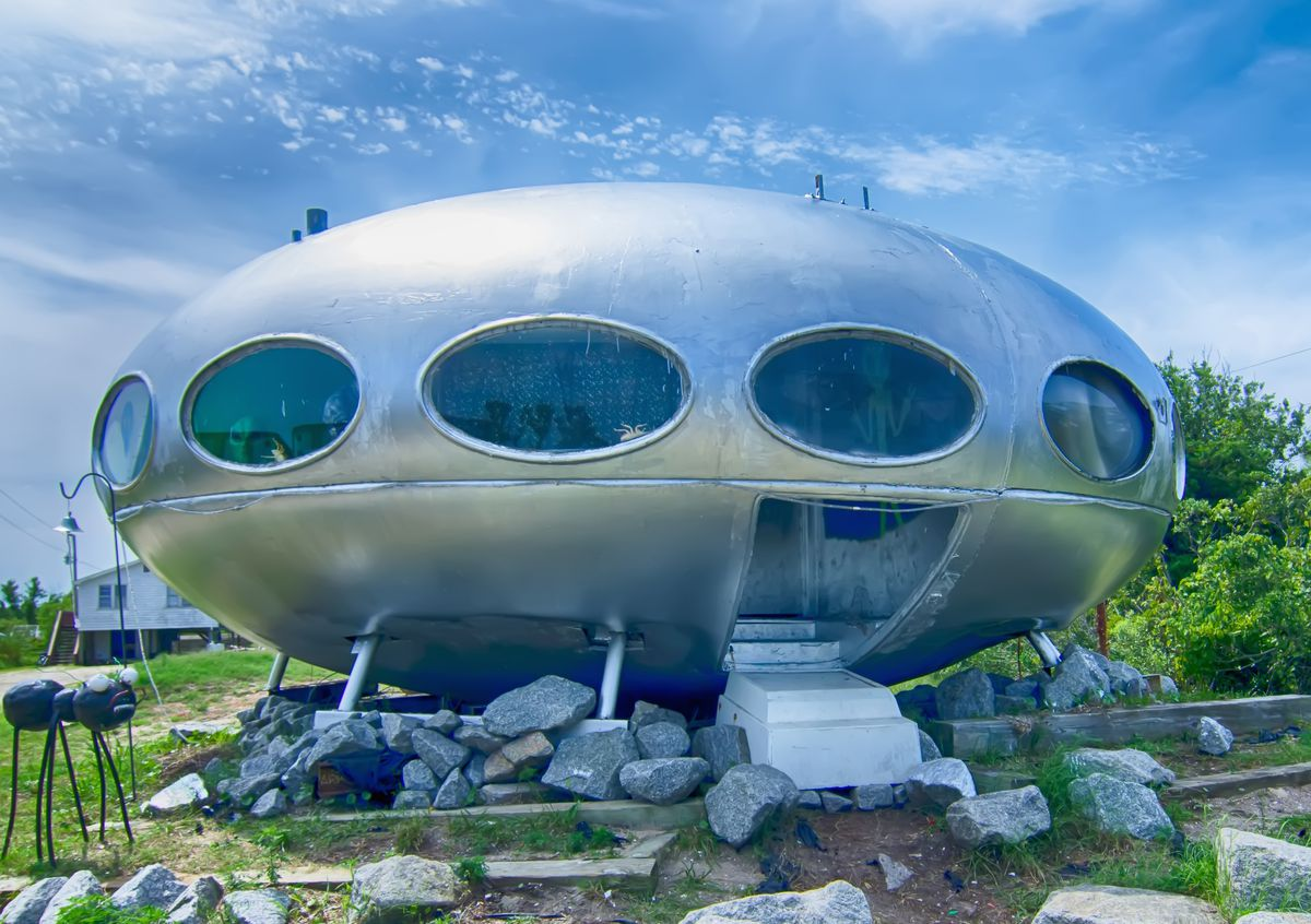 The exterior of a Futuro House in North Carolina. The facade is metallic silver with oval windows. The house is perched on a bed of rocks.