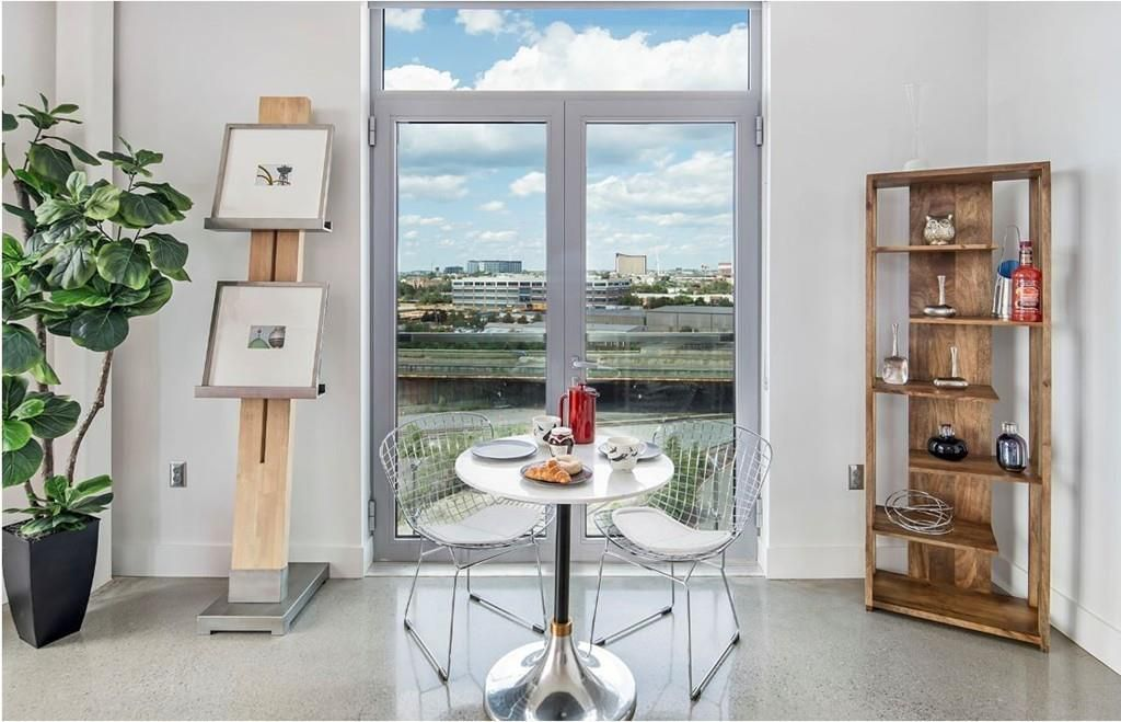 A table and two chairs next to a double easel and overlooking a cityscape through two closed glass doors.