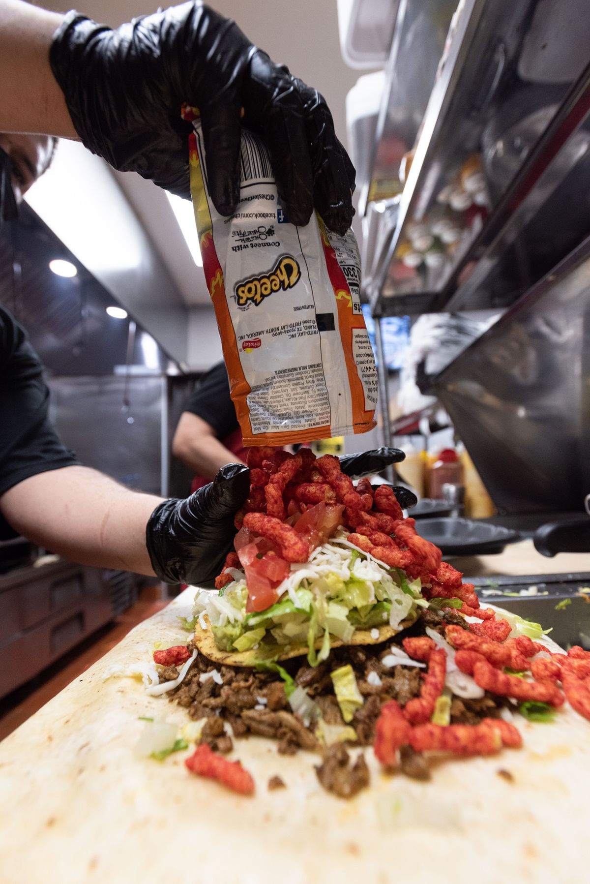 A worker drops Hot Cheetos on top of a burrito inside a restaurant.