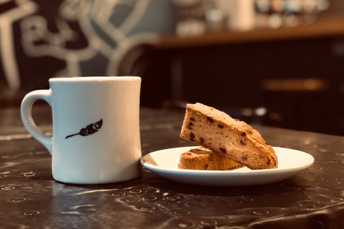 A white coffee mug with a black feather printed on the side and a plate of biscotti.