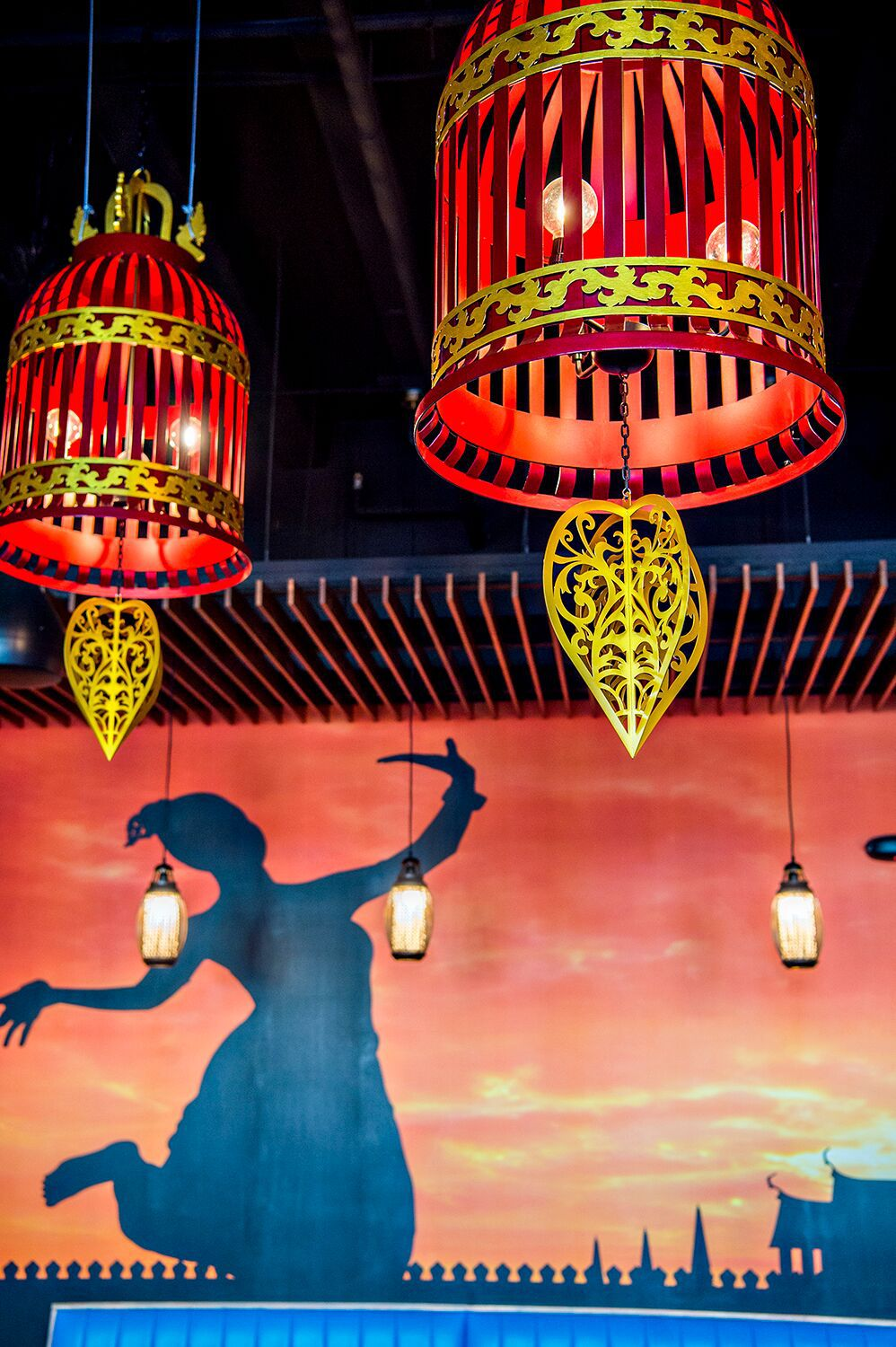 A photo of a close up view of the large red lamps with the silhouette of a dancing woman visible in the mural behind them