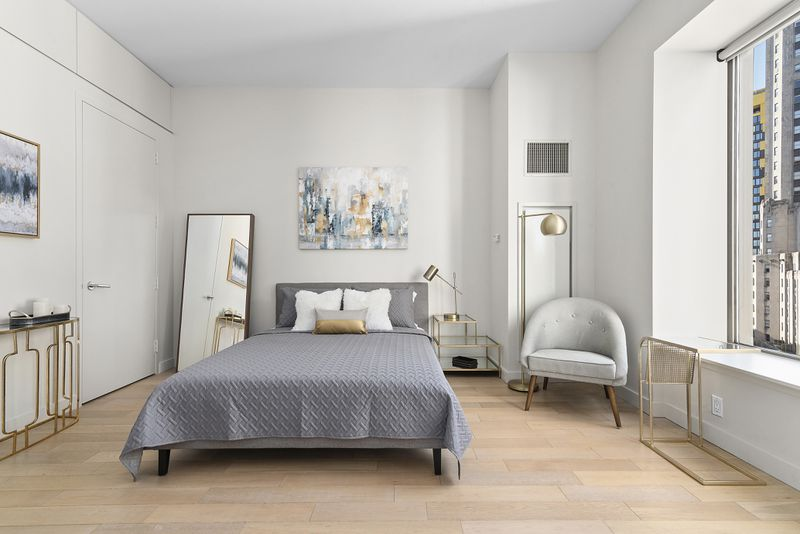 A bedroom with a large bed, a large window, white walls, and hardwood floors.