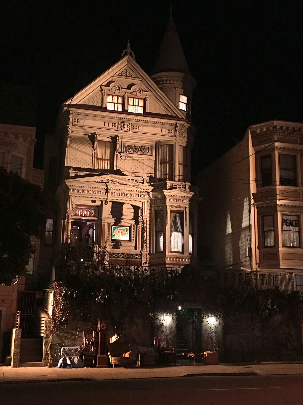 A white, detailed Victorian home at night, with lights on in the windows.