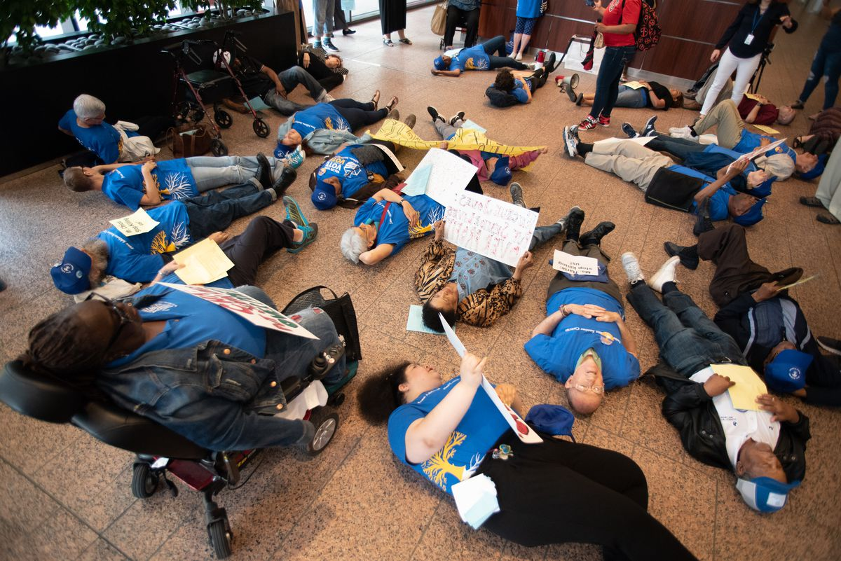 """Senior residents stage a """"die-in"""" in the lobby of the Chicago Housing Authority's downtown office during a board meeting. 