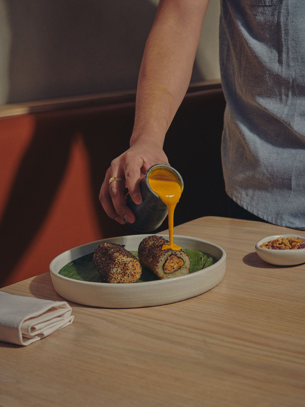 A chef pours orange, chile-laced walnut sauce over cylindrical chicken and seaweed maki rolls