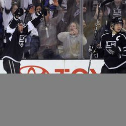 Los Angeles Kings defenseman Alec Martinez, top left, celebrates his goal as San Jose Sharks defenseman Justin Braun falls to the ice and Kings right wing Dustin Brown, front right, looks on during the first period of an NHL hockey game, Thursday, April 5, 2012, in Los Angeles.