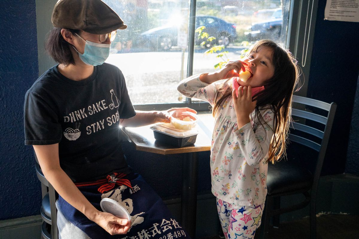 A little girl eats a bite of food with her mother, in a mask, next to her.
