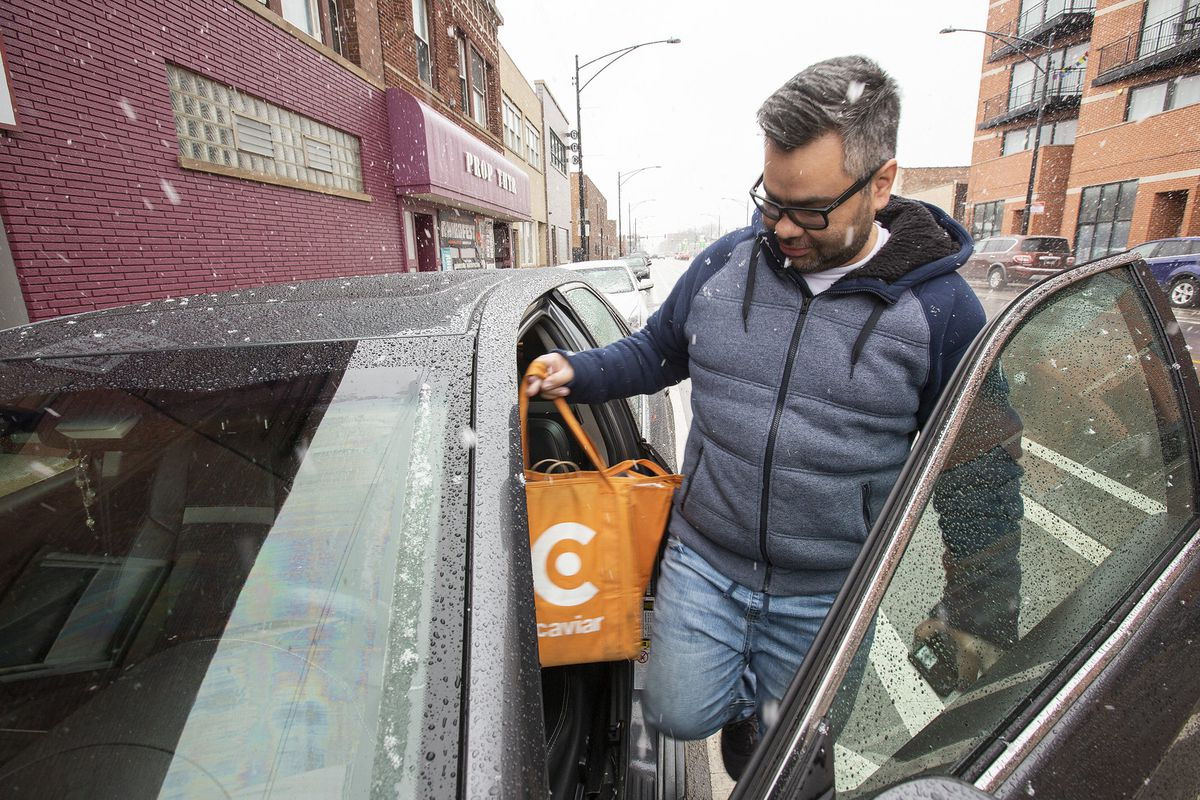 A person with an orange bag full of food stepping into his sedan with a door open.