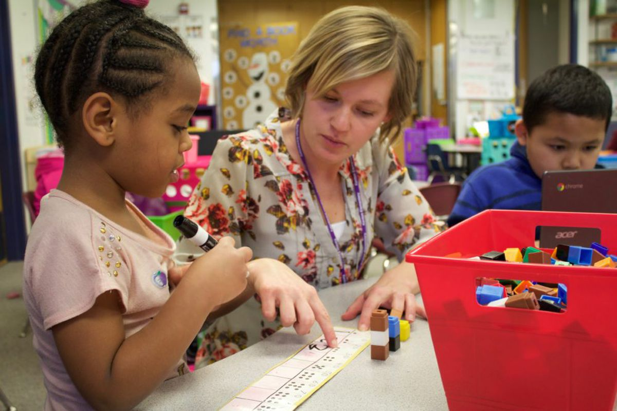 A kindergarten teacher at Kenton Elementary in Aurora, Colorado helps a student practice saying and writing numbers.