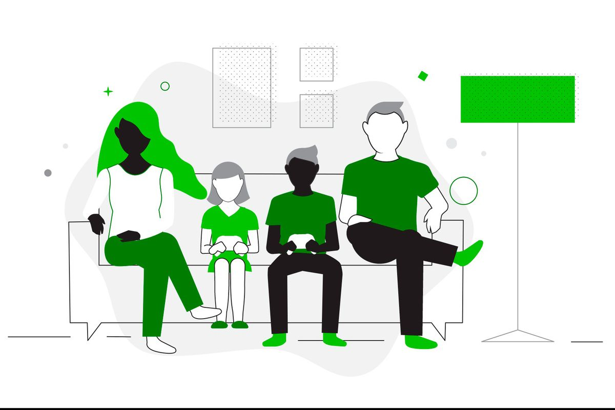 A family sits together in the living room, playing games with controllers.