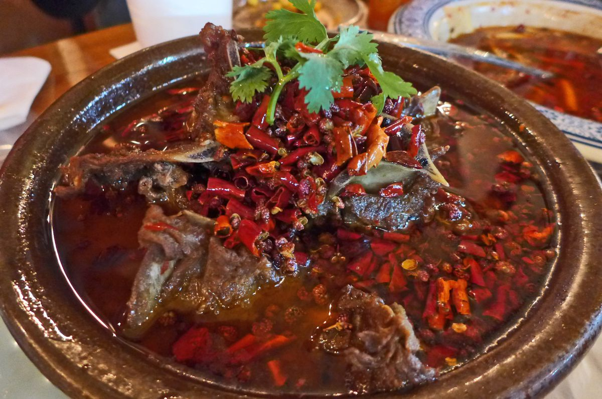 A ceramic bowl filled with red oil and red dried peppers, with brown meat bones barely visible ont he surface.