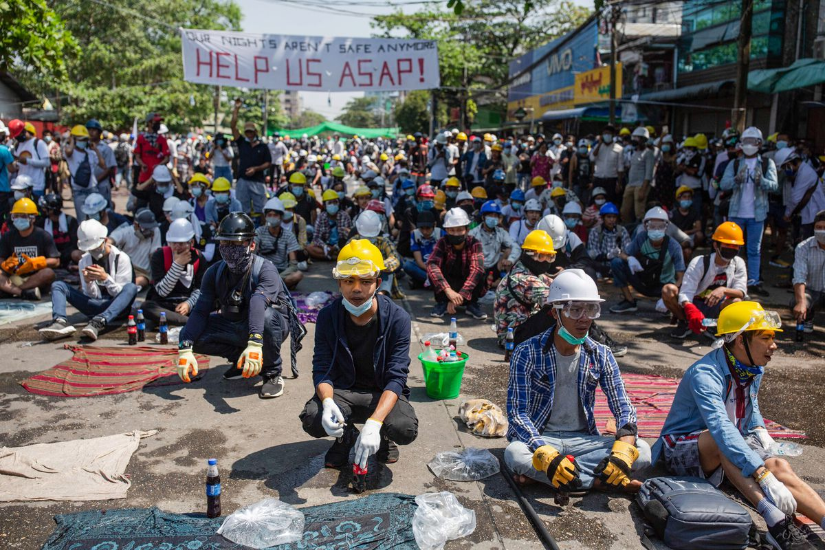 Protesters hold wet pieces of cloth and plastic bags of...