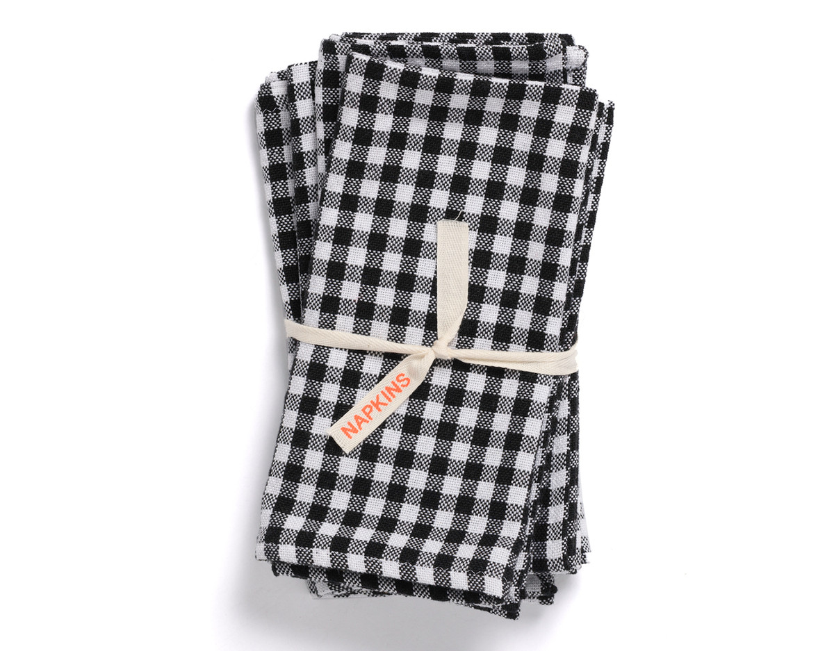 A stack of black and white patterned napkins. The napkins are held together with a white ribbon that has a tag which reads: napkins.
