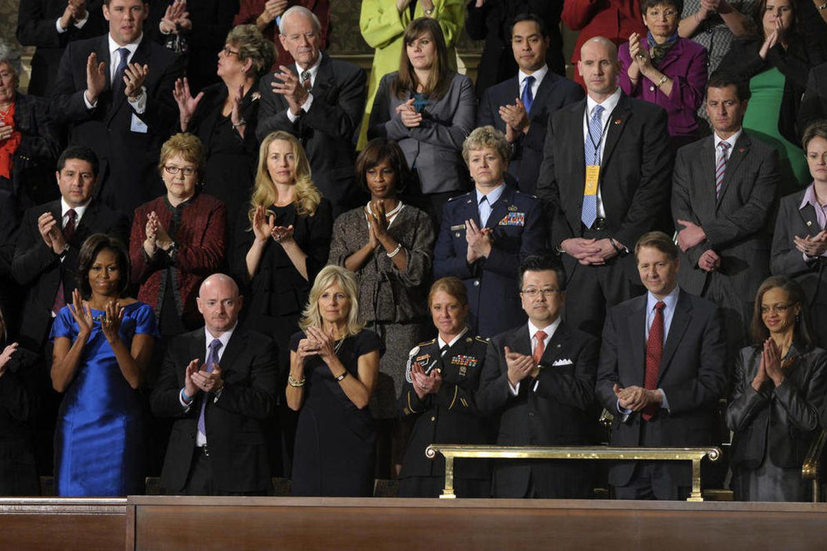 CORRECTS THAT MAN IS SIXTH FROM LEFT IN FIRST ROW TO HIROYUKI FUJITA--First lady Michelle Obama and guests applaud during President Barack Obama's State of the Union address on Capitol Hill in Washington, Tuesday, Jan. 24, 2012. Front row, from left are,